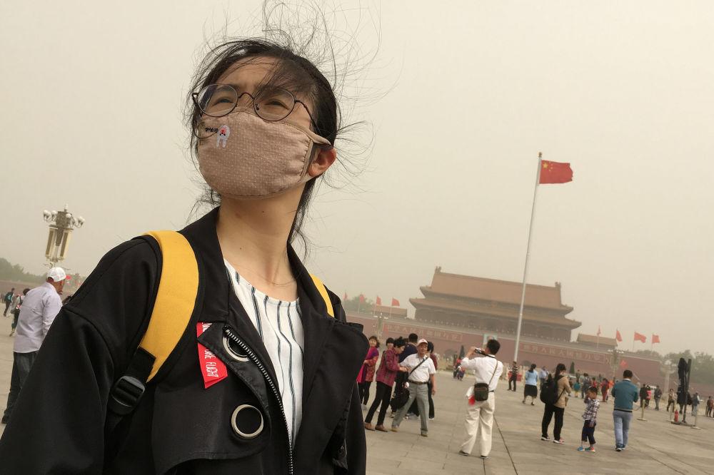 Una ragazza porta una maschera per proteggersi dallo smog. Piazza Tiananmen, Pekino, Cina.