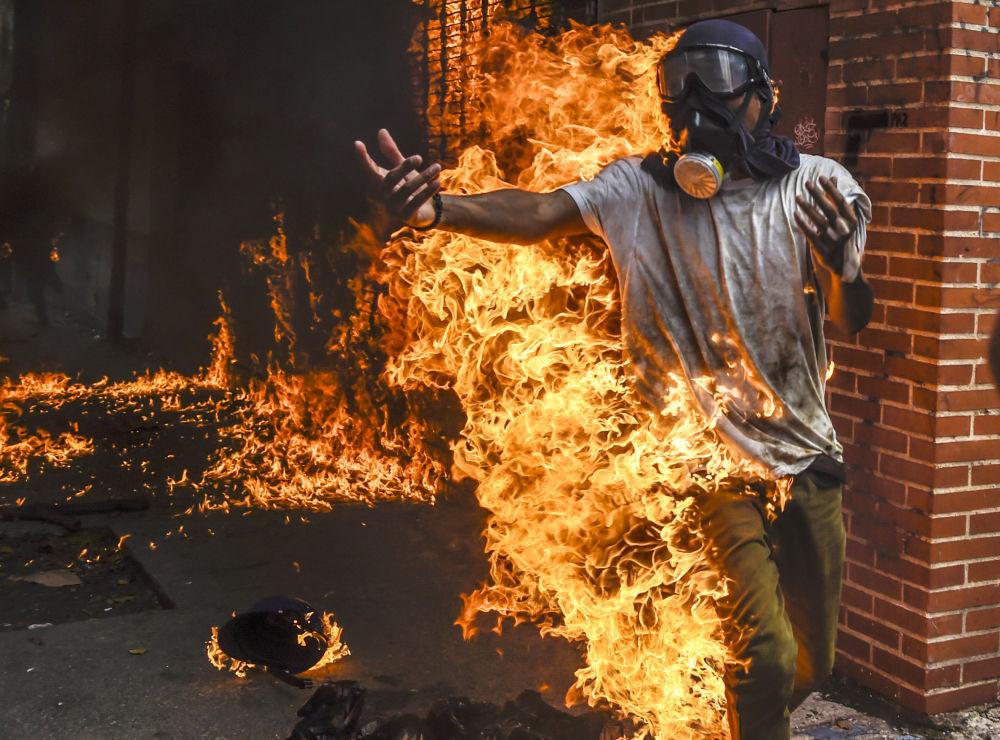 Un manifestante ha preso fuoco durante le manifestazioni contro il presidente della Venezuela Nicolas Maduro a Caracas.