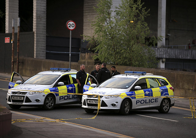 Police officers stand next to their vehicles near the Manchester Arena after a blast at Ariana Grande concert Tuesday May 23, 2017