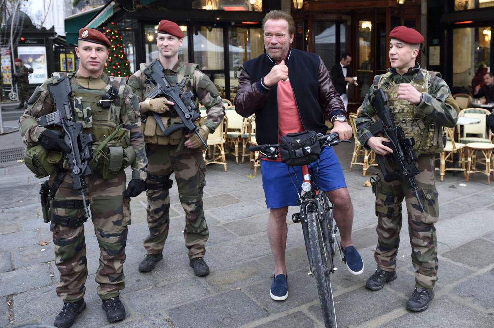 L'ex governatore di California Arnold Schwarzenegger con soldati francesi a Parigi.