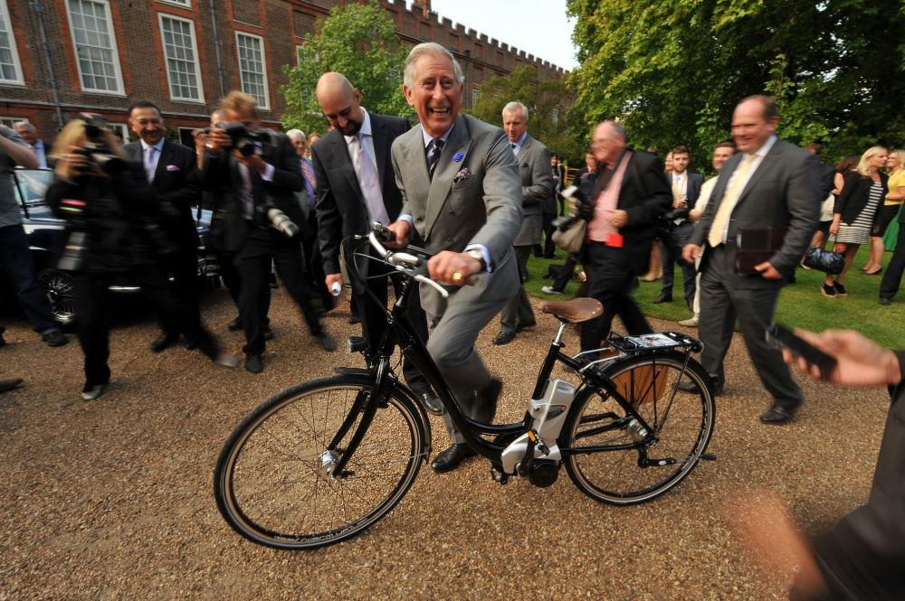 Carlo, principe di Galles va in bicicletta elettrica nel centro di Londra.