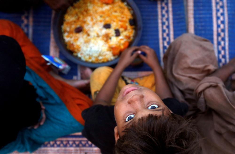 Un ragazzo aspetta il cibo durante il Ramadan in Pakistan.
