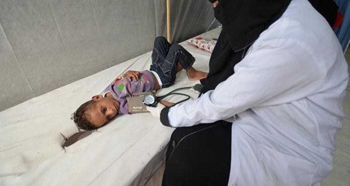 Infermiera assiste bambina affetta da colera nello Yemen