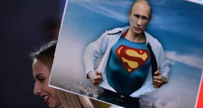 Un giornalista tiene un cartellino con l'immagine di Vladimir Putin prima della linea diretta con il presidente (foto d'archivio)