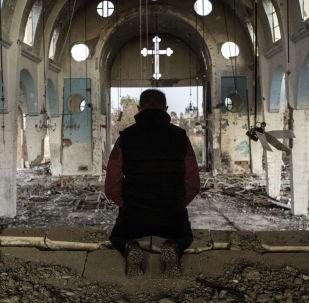 Un abitante di uno dei villaggi nella provincia di Al-Hasakah a nord-est della Siria sta in preghiera nella chiesa di San Giorgio, distrutto dal Daesh.