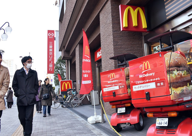 Pedestrians walk past a McDonald's fast-food restaurant in Tokyo on January 9, 2015