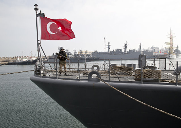 A Turkish marine serviceman stands on the deck of a Turkish navy TCG Turgutreis vessel