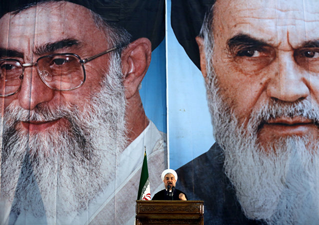 Iranian President Hassan Rouhani delivers a speech under portraits of Iran's supreme leader, Ayatollah Ali Khamenei (L) and Iran's founder of the Islamic Republic, Ayatollah Ruhollah Khomeini (R), on the eve of the 25th anniversary of the Islamic revolutionary leader Ayatollah Ruhollah Khomeini's death, at his mausoleum in a suburb of Tehran