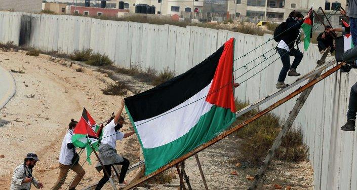 Attivisti stranieri e palestinesi attraversano il muro di israele.
