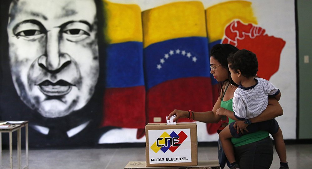A  woman holds her infant as she casts her vote in front of a mural of the late Venezuelan President Hugo Chavez at a polling station during the Constituent Assembly election in Caracas, Venezuela, July 30, 2017.