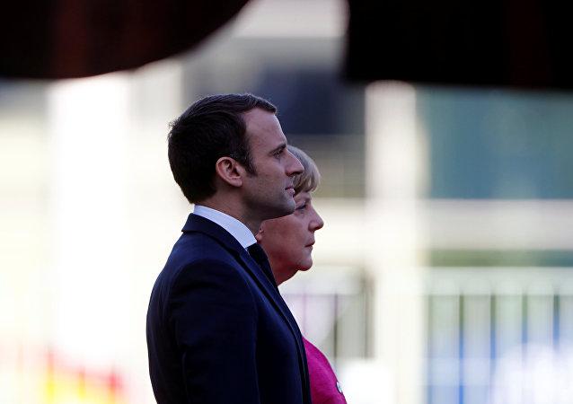 La cancelliera tedesca Angela Merkel e il presidente francese Emmanuel Macron ascoltano gli inni nazionali a Berlino.