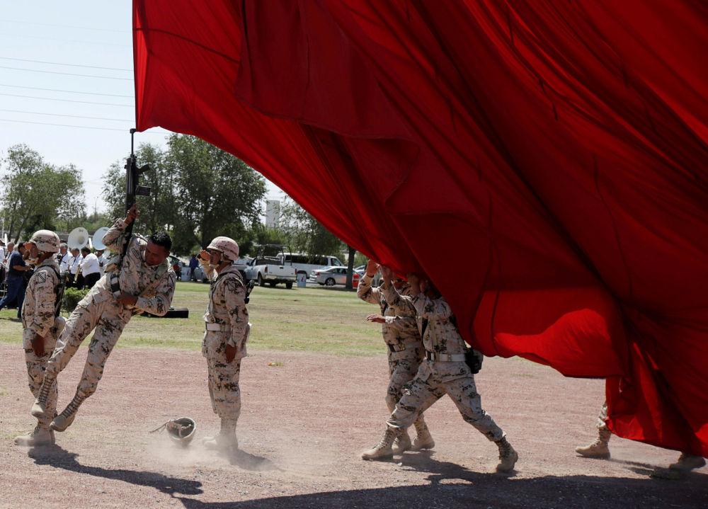 Un soldato e la bandiera nazionale gigante durante le preparazioni per il 207° anniversario dell'indipendenza del Messico dalla Spagna a Ciudad Juarez, Messico.