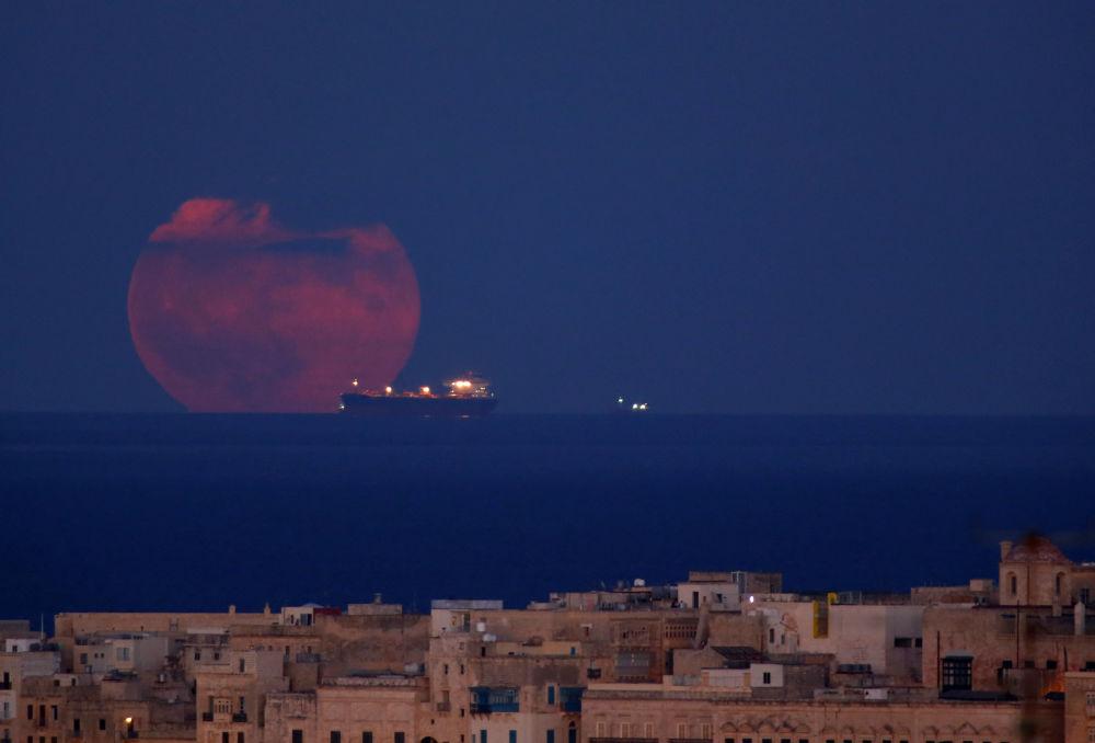 Una petroliera sullo sfondo della luna piena vicino alle coste di Valletta, Malta.