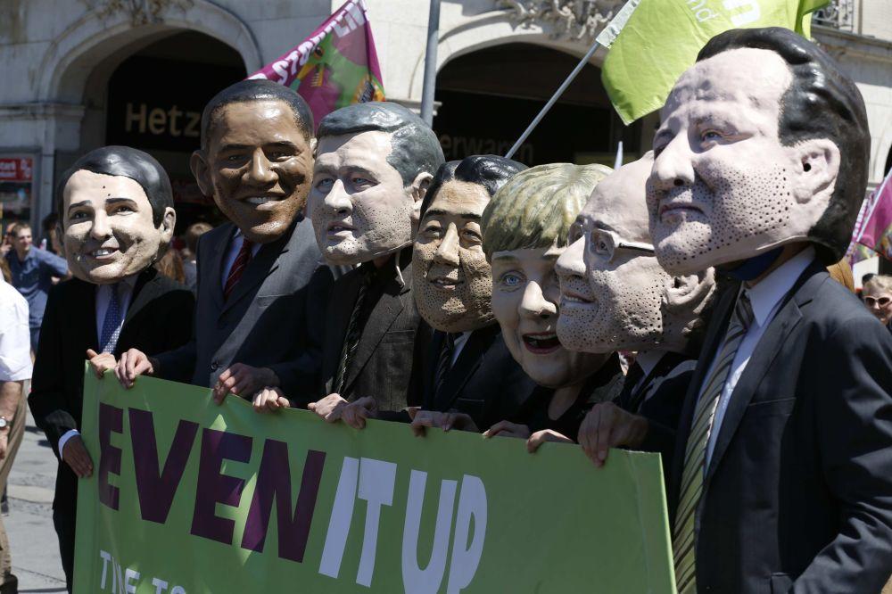 Le maschere che rappresentano le facce dei politici durante le proteste contro il vertice di G7 a Monaco