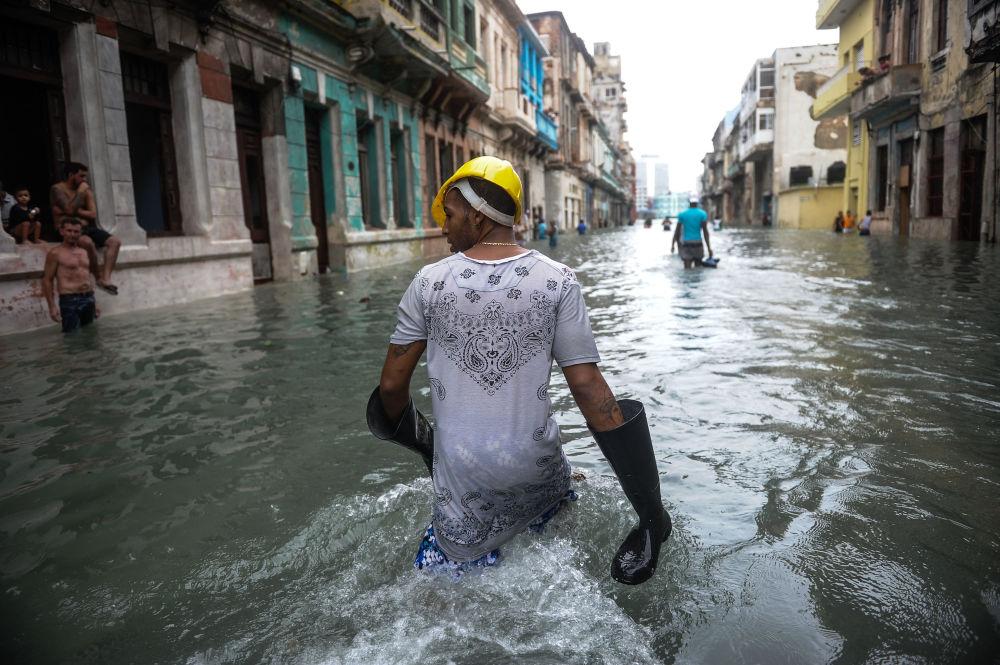 Un cubano ad una strada allagata ad Havana.