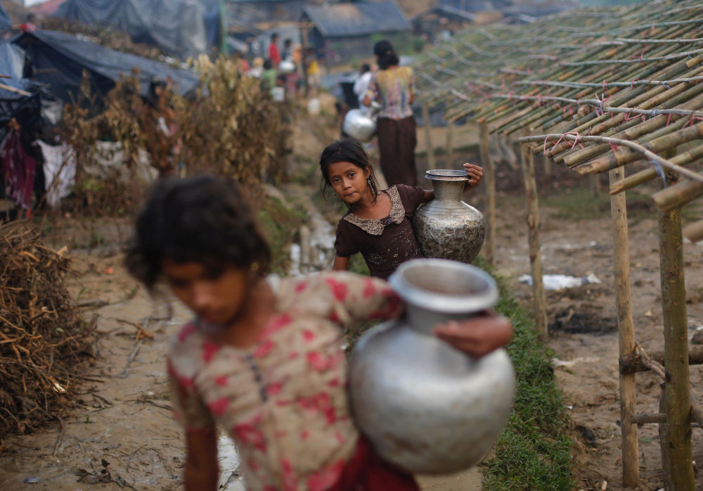 Le ragazze rifugiate portano bricchi d'acqua a Bangladesh.