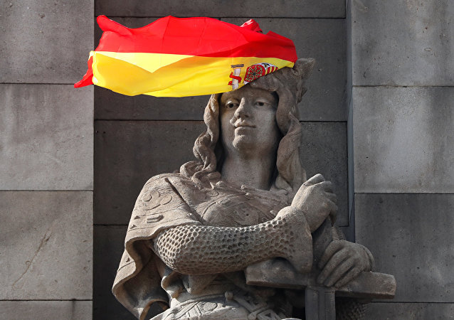 A Spanish flag hangs over the face of a figure representing one of the four realms of Spain on the statue to Columbus in Barcelona, Spain, October 11, 2017.