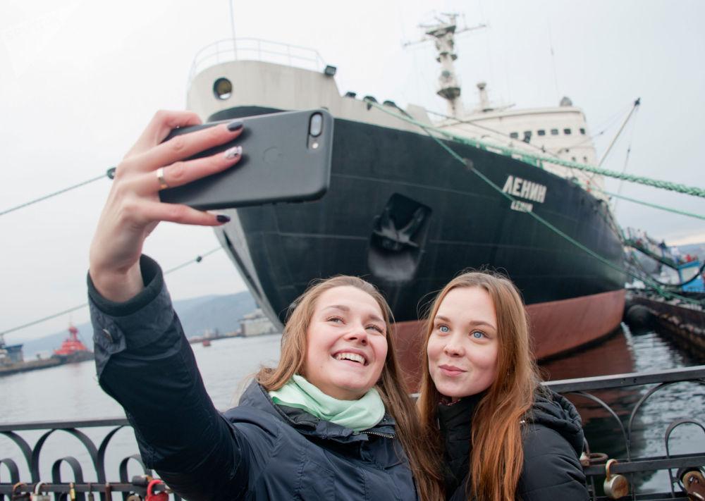 Ragazze si fanno foto di fronte al museo-rompighiaccio Lenin a Murmansk, Russia.