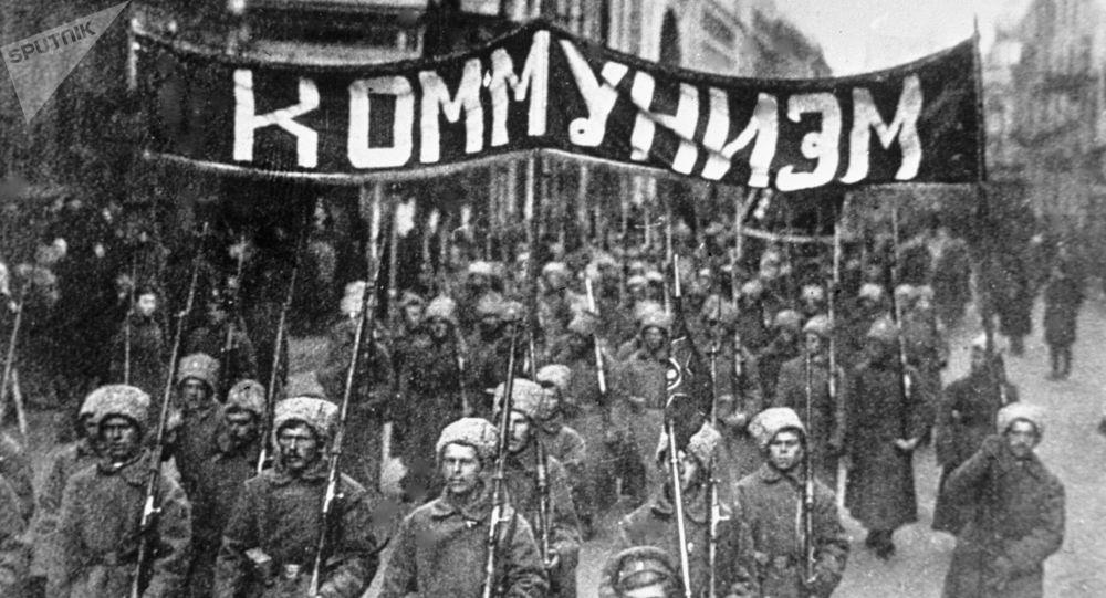 Una colonna dei soldati con il cartellone con la scritta comunismo su una strada di Mosca, il 1917.