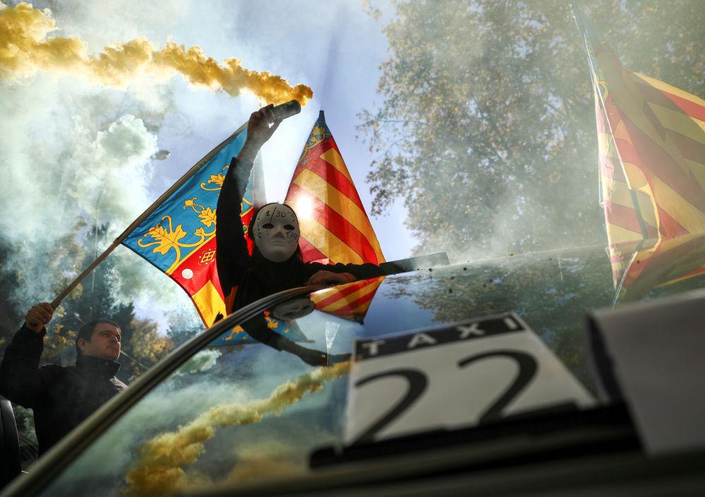 Un uomo in maschera tiene un fumogeno durante lo sciopero dei taxi a Madrid.