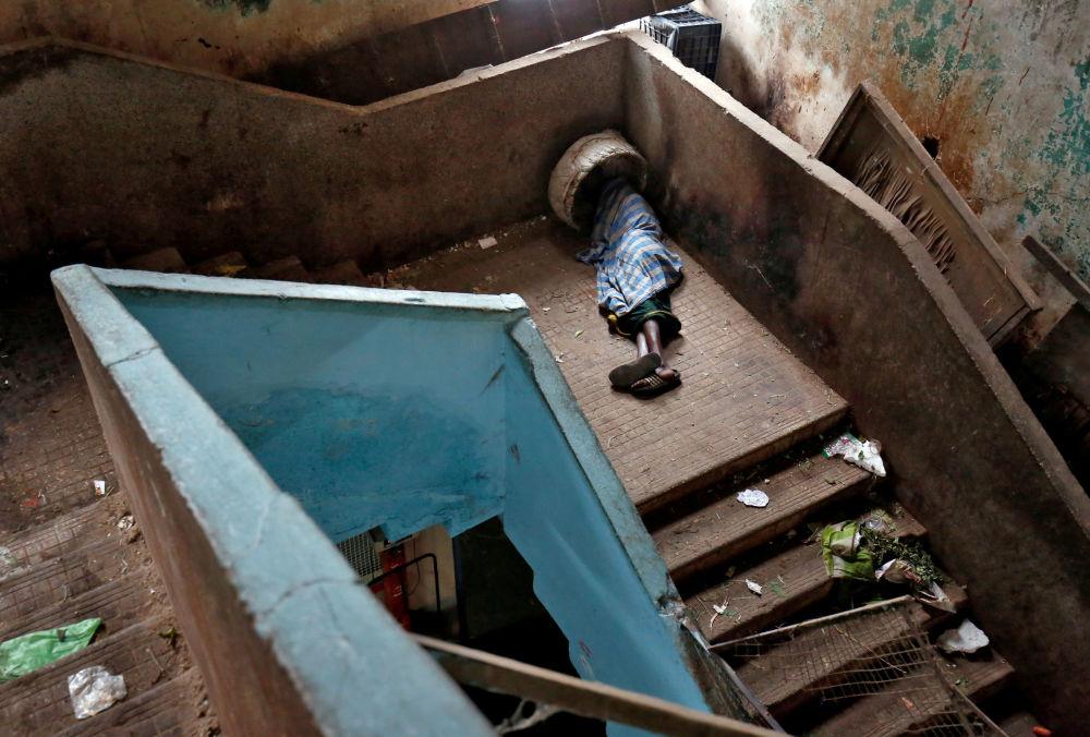 Un mendicante dorme sulle scale in un mercato di Bengaluru, India.