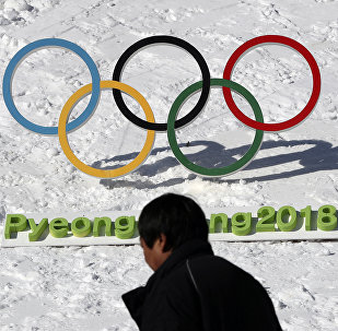 In this Feb. 3, 2017 photo, a man walks by the Olympic rings with a sign of 2018 Pyeongchang Olympic and Paralympic Winter Games in Pyeongchang, South Korea