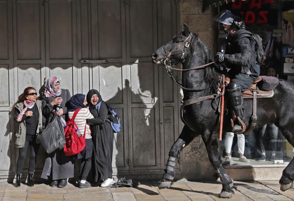 Donne spaventate stanno vicino al poliziotto israeliano armato a Gerusalemme est.