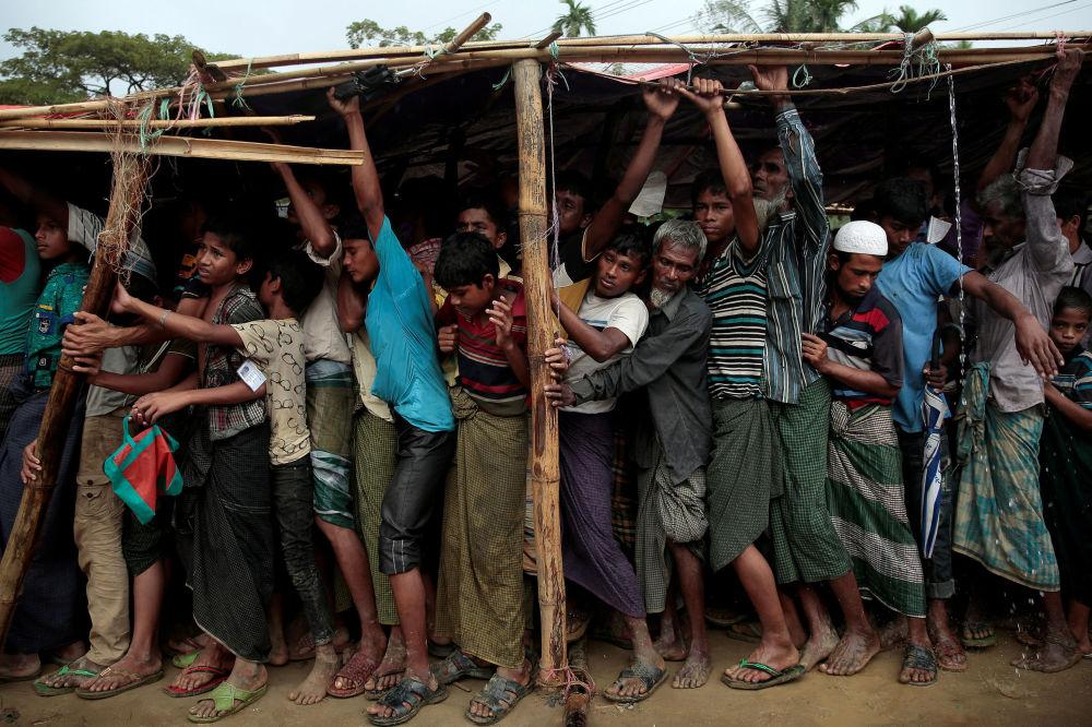 Rifugiati Rohingya fanno la fila per avere le coperte nel campo di Balukhali, Bangladesh.