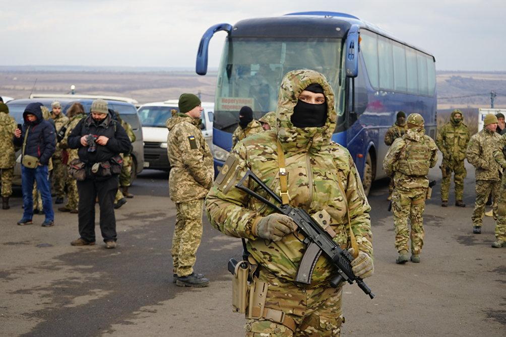 Soldati ucraini coi volti nascosti sorvegliano le operazioni
