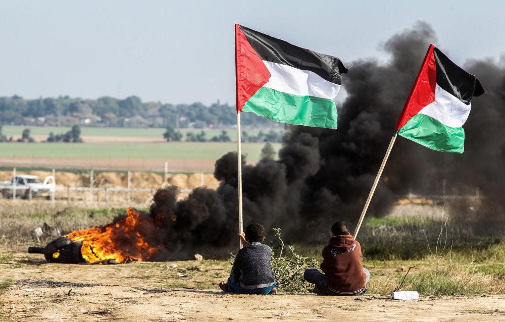 Manifestanti palestinesi con le bandiere nazionali alla frontiera tra l'Israele e Gaza.