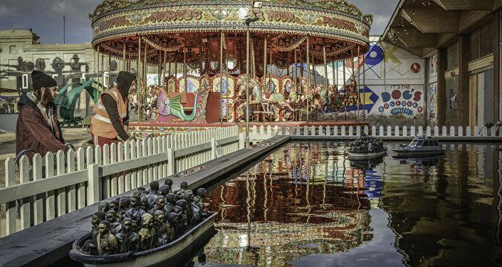 Uno stagno con le barche piene di rifugiati a Dismaland, o parco divertimenti anti-Disneyland di Banksy.