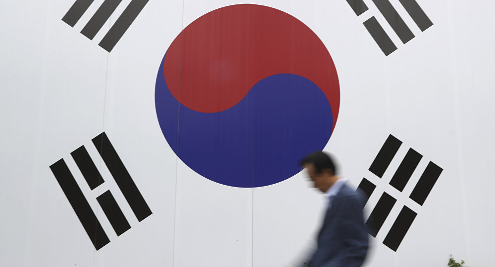 A man walks by a huge national flag printed on the wall in Seoul South Korea Wednesday Oct. 26 2016