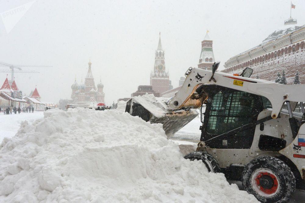 Gli operai del servizio pubblico puliscono dalla neve la Piazza Rossa di Mosca.