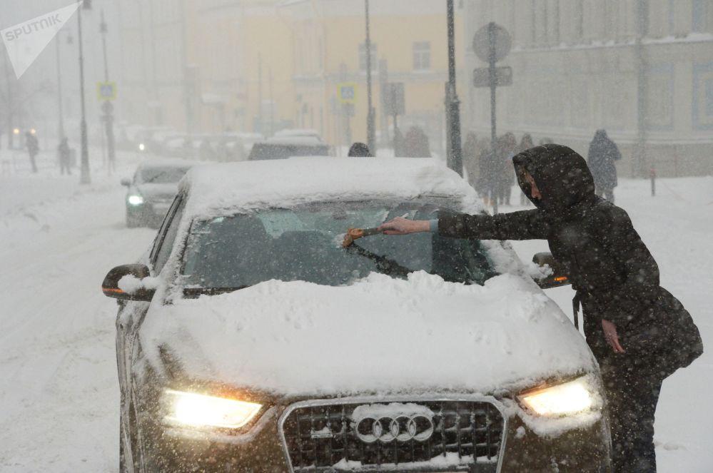 Una donna pulisce la sua automobile.
