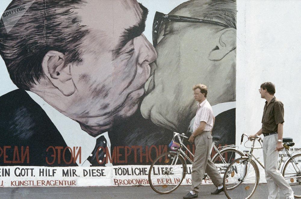 Berlinesi guardano una parte del Muro di Berlino rimasta indistrutta dipinta da un pittore.
