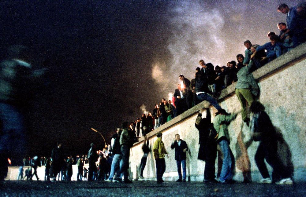 Gli abitanti di Berlino Est al Muro di Berlino dopo l'apertura delle frontiere tra le parti Est ed Ovest della città, 1989.