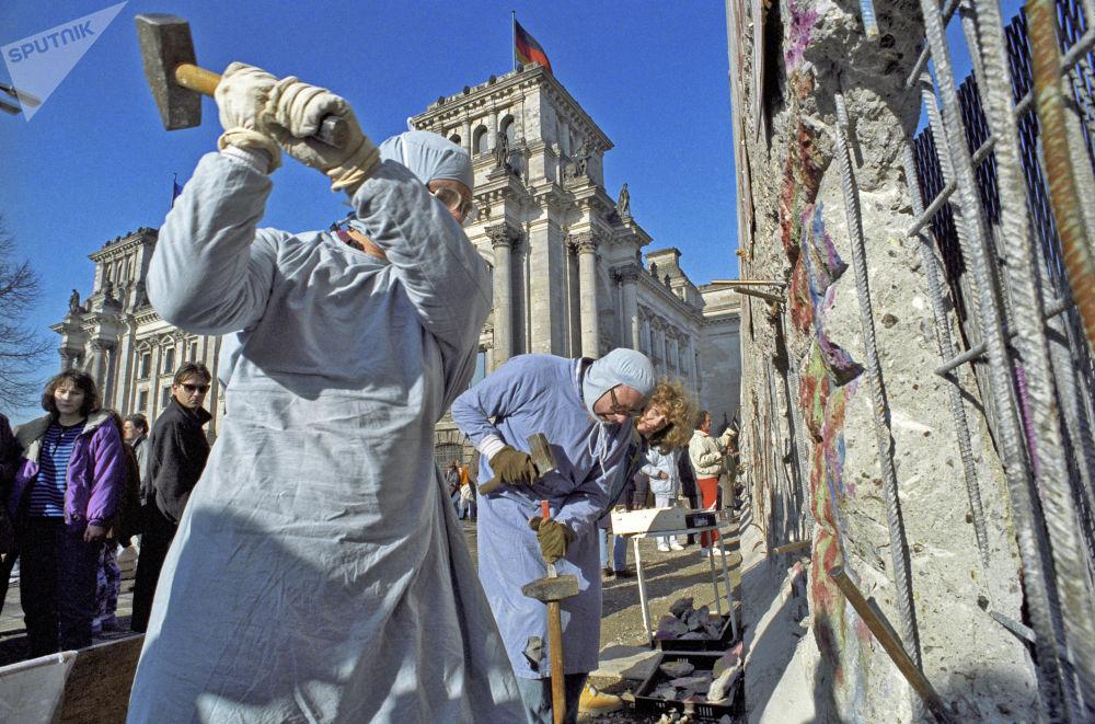 Gli abitanti della Germania Est si prendono i souvenir dal Muro di Berlino, 1990.