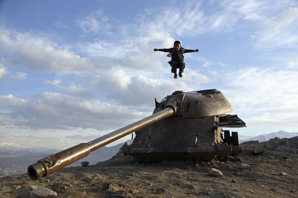 Un ragazzo afghano salta da un carro armato nei pressi di Kabul.