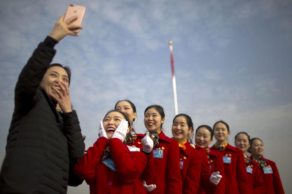 Ragazze-hostess si fanno un selfie durante le seduta della riunione pancinese dei rappresentanti popolari a Pechino.