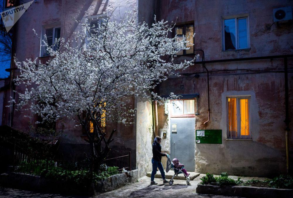 Una donna con sua figlia viste all'uscita di una casa residenziale a Sebastopoli, Crimea, Russia.