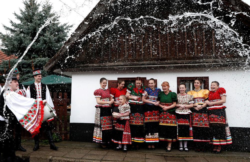 Uomini annaffiano le donne con l'acqua durante le celebrazioni di Pasqua a Mezokovesd, Ungheria.