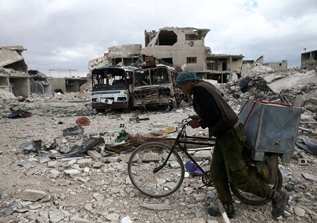 A man walks with his bicycle at a damaged site in the besieged town of Douma, Eastern Ghouta, in Damascus, Syria