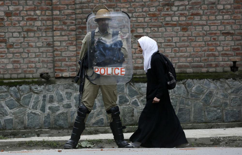 Una studentessa musulmana passa di fronte a un poliziotto indiano durante le proteste contro i casi dello stupro a Srinagar, Kashmir.