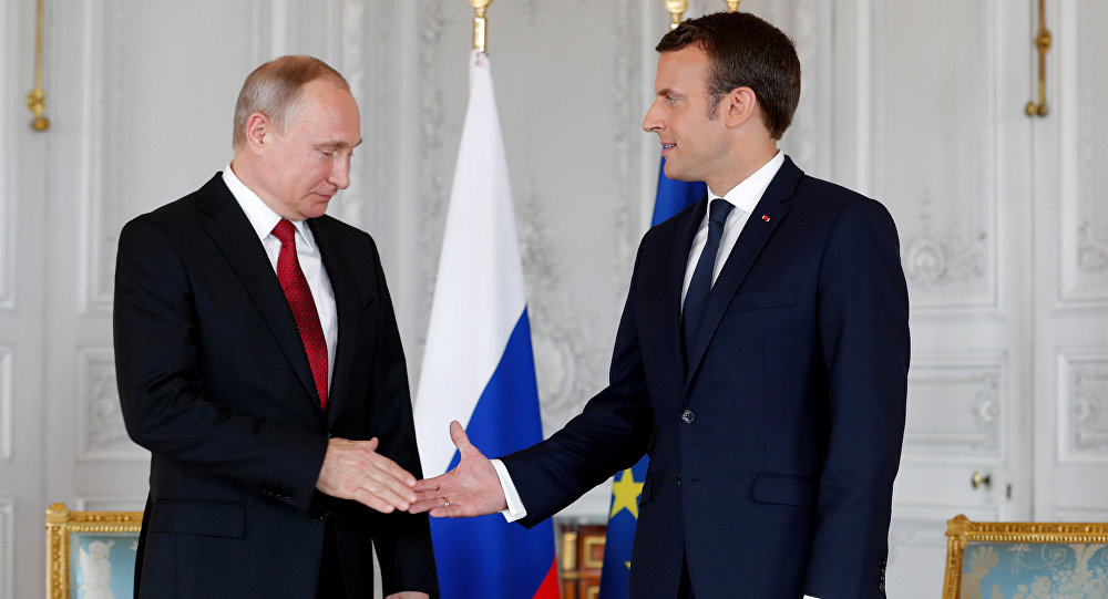 French President Emmanuel Macron shakes hands Russian President Vladimir Putin (L) at the Chateau de Versailles as they meet for talks before the opening of an exhibition marking 300 years of diplomatic ties between the two countyies in Versailles, France, May 29, 2017