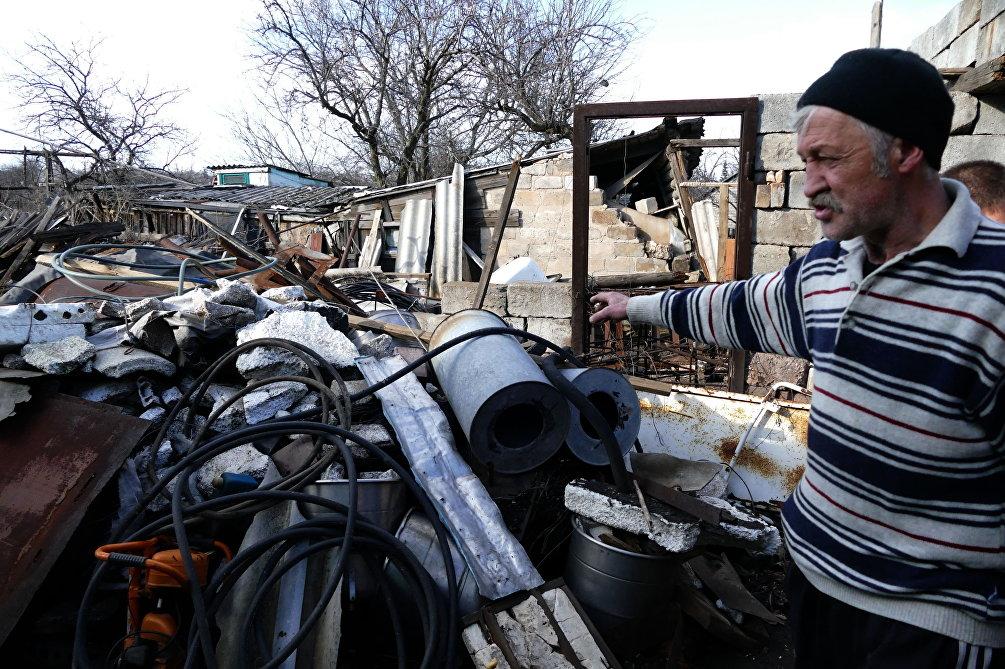 Un abitante di Zaytsevo vicino a quello che resta della sua abitazione