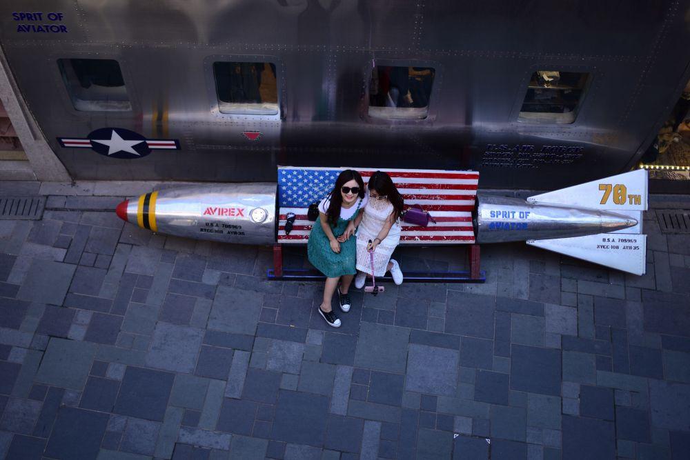 Ragazza si fanno fotografare su una panchina-missile in un negozio di Pechino.