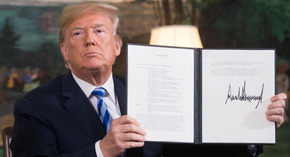 Il presidente USA Donald Trump tiene il documento firmato che riprende le sanzioni contro l'Iran