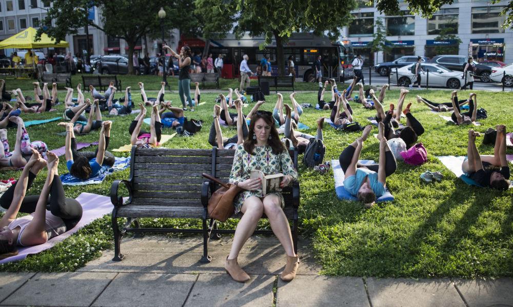 Una donna legge un libro mentre attorno di lei si svolge una lezione di yoga a Washington, USA.
