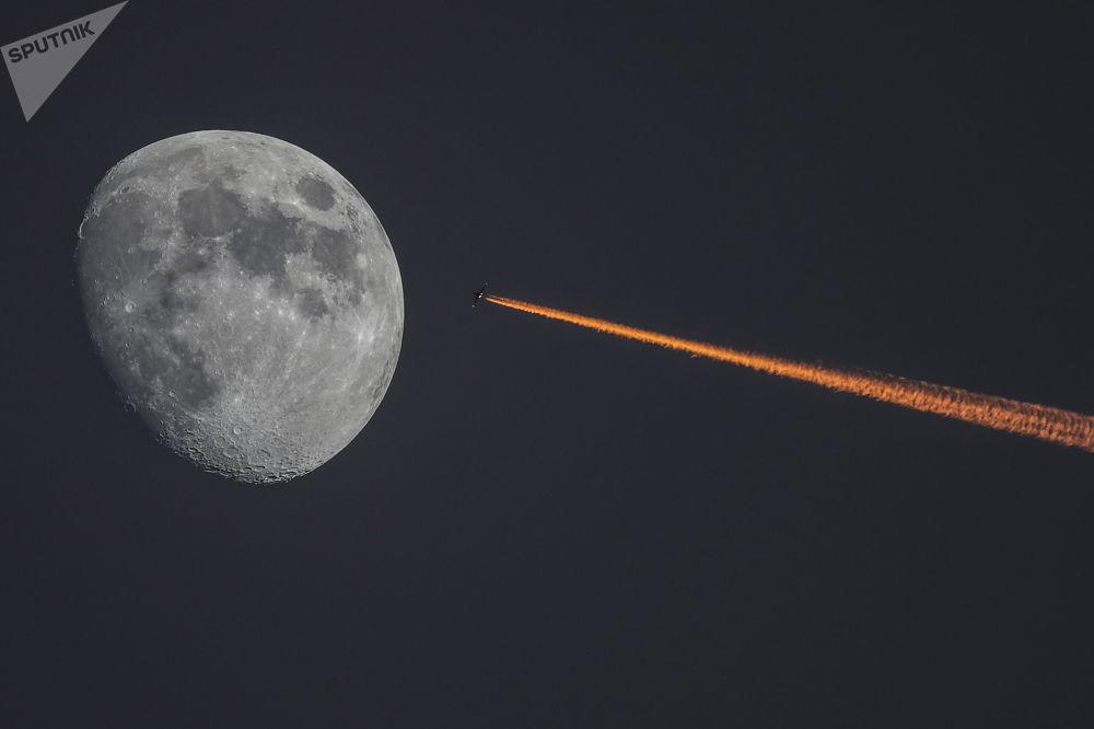 La Luna e un aereo al tramonto.