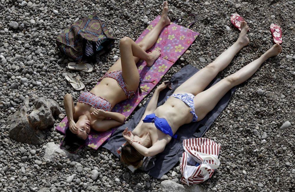 Donne si abbronzano durante la gran prix di Formula 1 in Monaco.